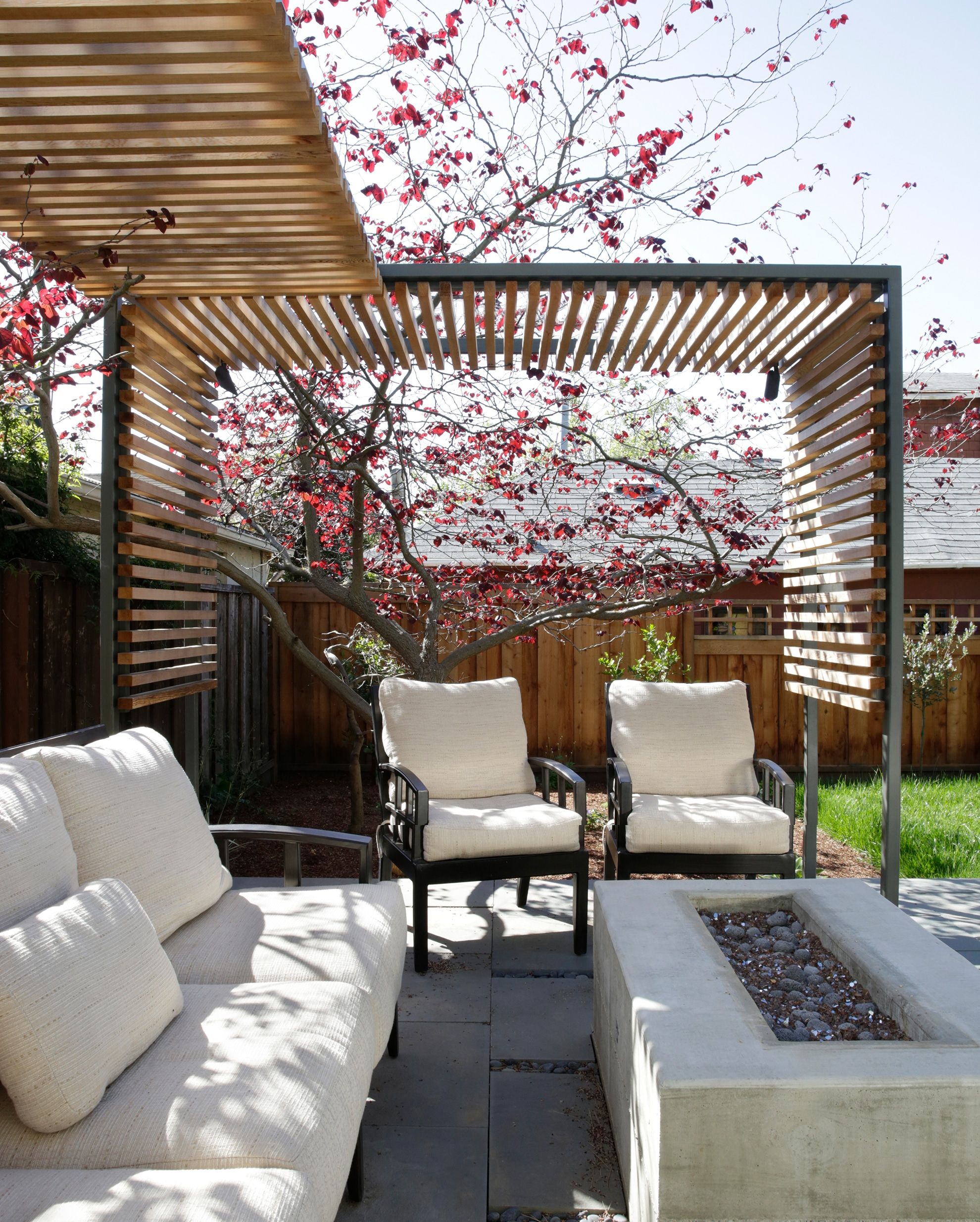 backyard trellis with seating in foreground